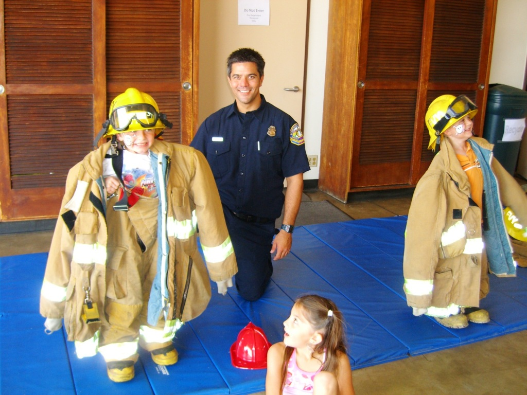 Children tyring on the firefighter uniform during