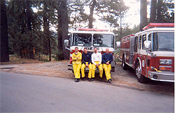 Firefighters posing for photo on the front of a fi